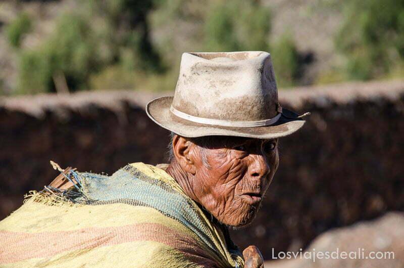 anciano peruano con saco a la espalda y cara llena de arrugas