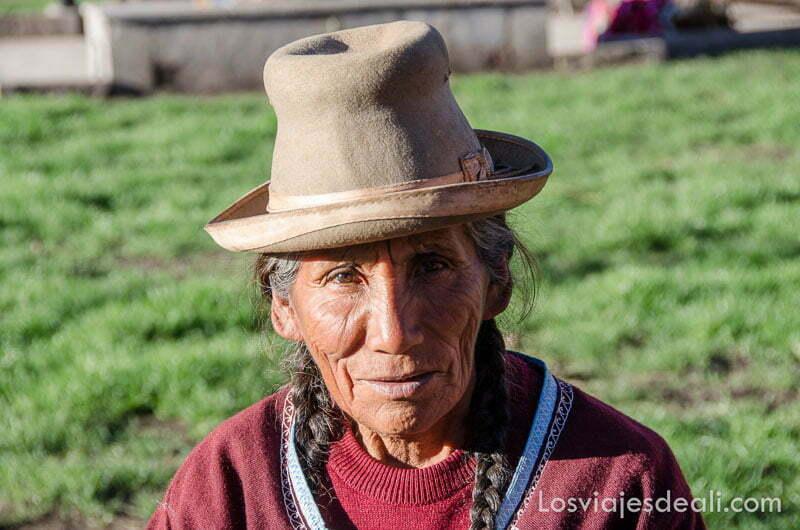 anciana peruana con sombrero y trenzas mirando de frente