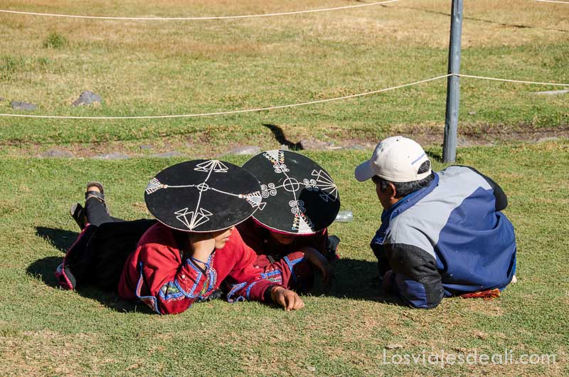 dos mujeres con sombreros negros con bordados blancos de ala ancha y plana tumbadas en la hierba hablando con un hombre