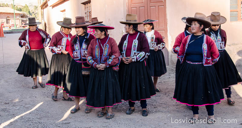 grupo de mujeres con falda negra chalecos rojos y sombreros marrones