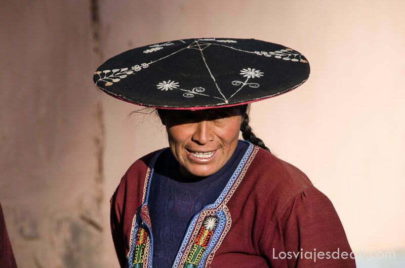 mujer sonriente con sombrero de ala ancha y plana de color negro con bordados blancos