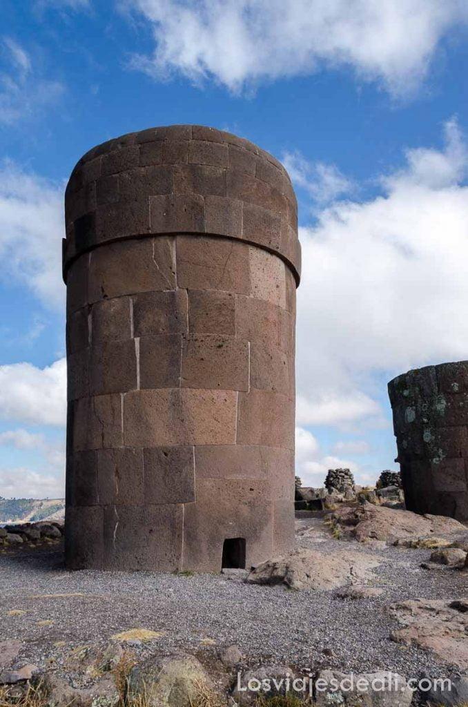 torre de piedra bajo cielo azul con nubes blancas