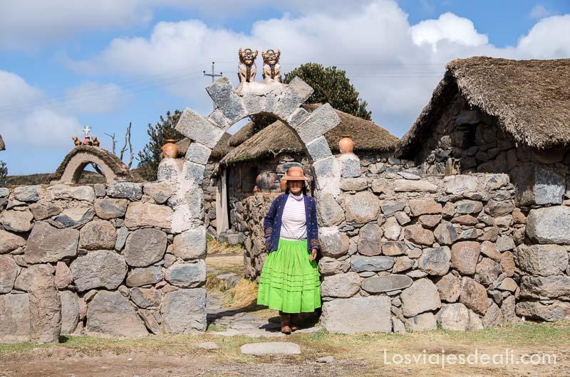 mujer con falda verde y  sombre hongo bajo arco de piedra con toros de cerámica arriba