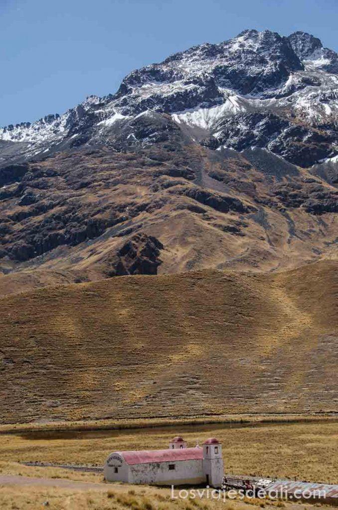 iglesia con dos campanarios con techo rojo en medio del altiplano con gran montaña detrás