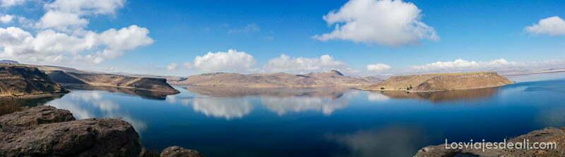 panorámica lago andino con montañas y nubes que se reflejan en el agua azul