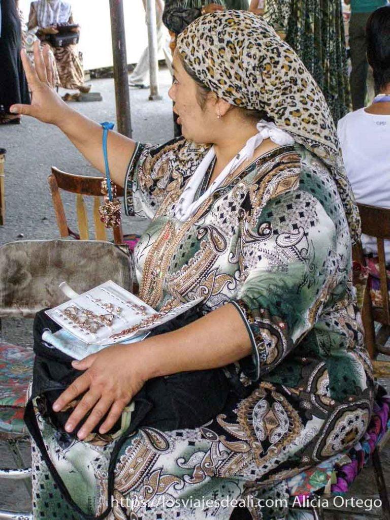 mujer ofreciendo sus joyas que lleva colgadas del cuello y en el regazo con vestido estampado y pañuelo en la cabeza
