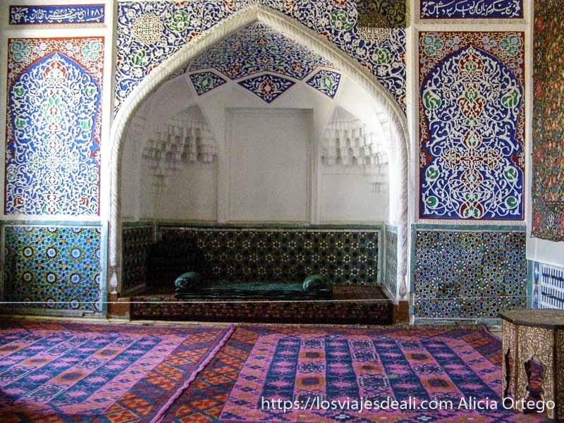 sala del mausoleo con alfombras y pared con azulejos