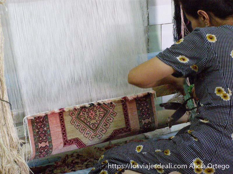 mujer tejiendo una alfombra en un telar