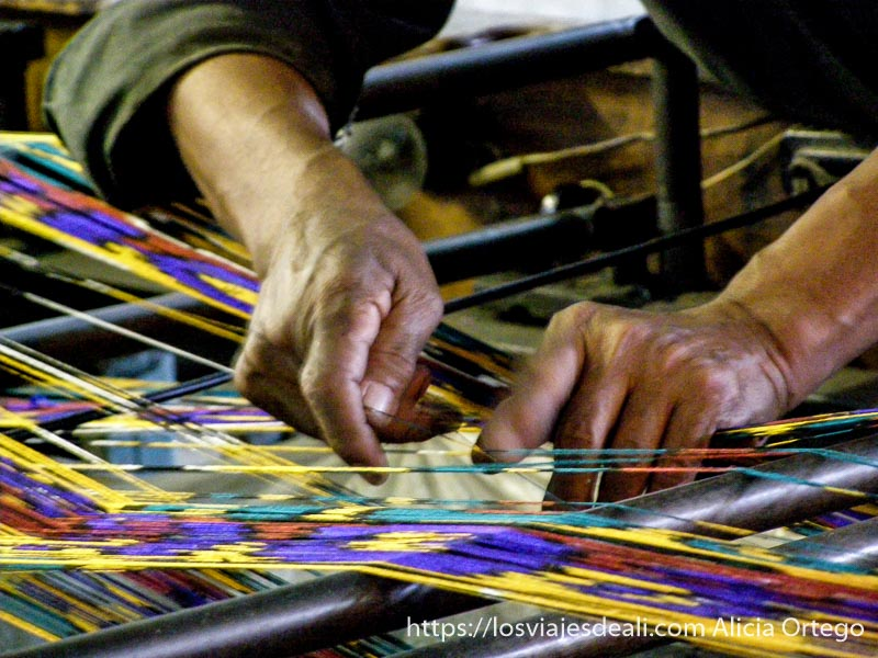 manos de hombre con hilos de colores en un telar