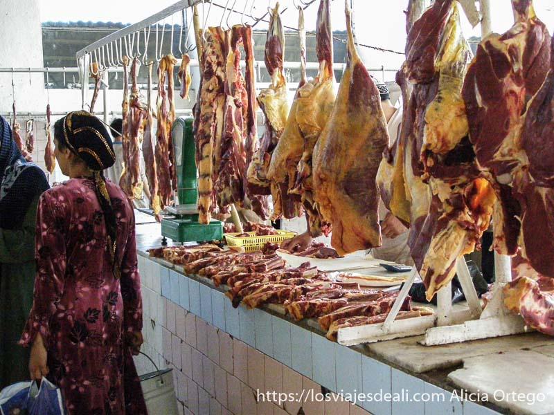 carnicería con piezas colgando y una mujer uzbeka con pañuelo en la cabeza