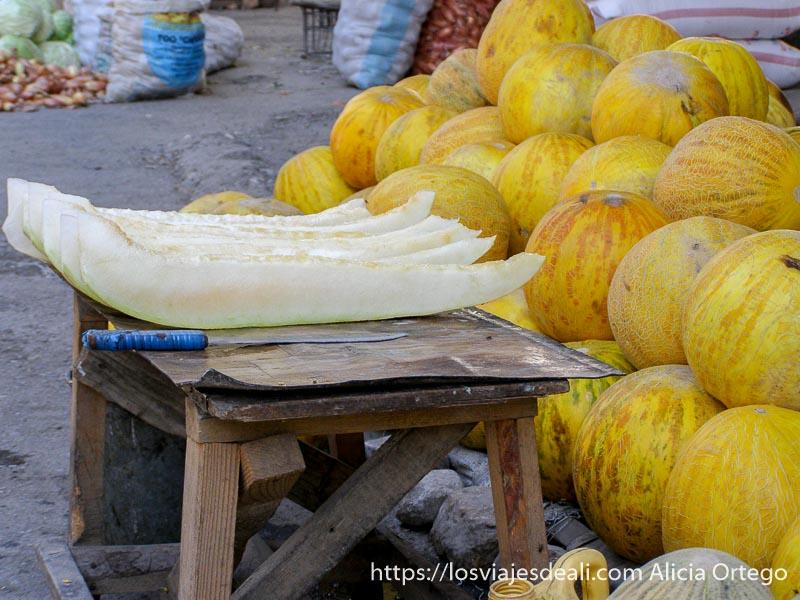 montón de melones amarillos redondos y una mesita con varias rajas de melón dispuestas para comer