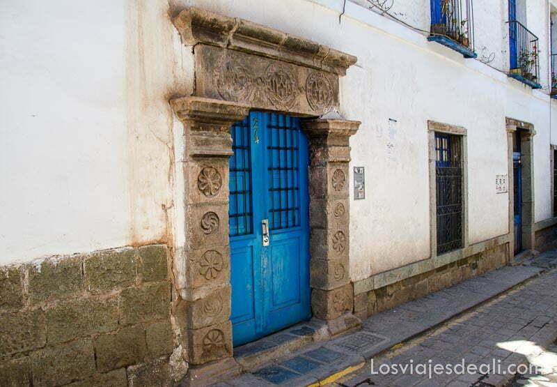 puerta con dintel de piedra y puerta azul en muro blanco