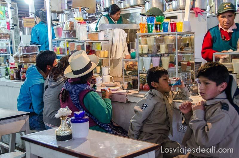 mujeres y niños en un puesto de comida del mercado