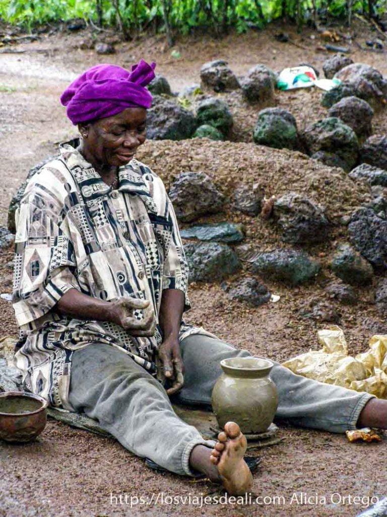 mujer anciana alfarera sentada en el suelo trabajando en una pequeña olla