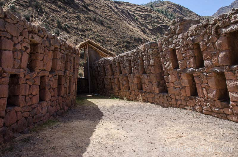 dos muros de piedra con ventanas que convergen en una puerta