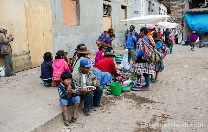 familia peruana comiendo sentados en la acera