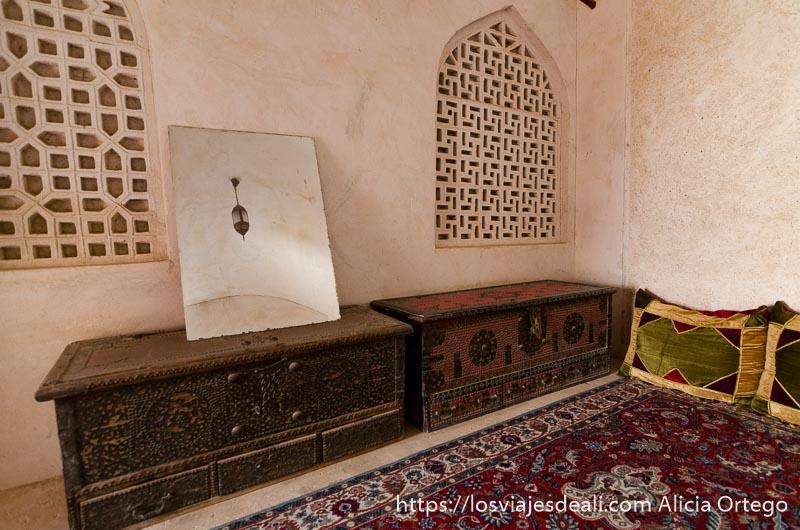 baúles sobre alfombras y un espejo que refleja la lámpara árabe