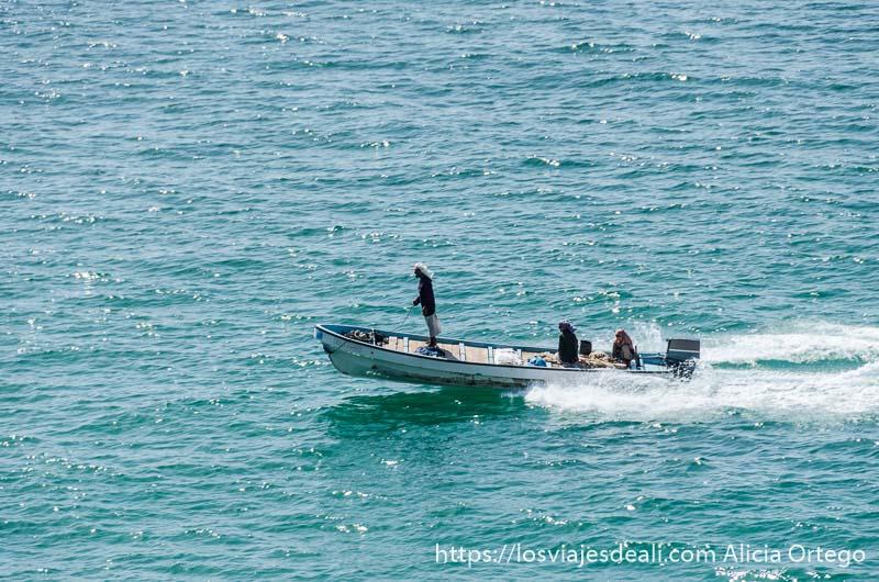 barca a motor surcando el agua con tres pescadores tapados para protegerse del sol y uno de ellos de pie en la proa