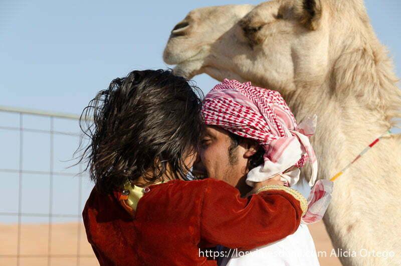 niña con vestido rojo de terciopelo en brazos de su padre con turbante rojo y blanco y un camello al lado