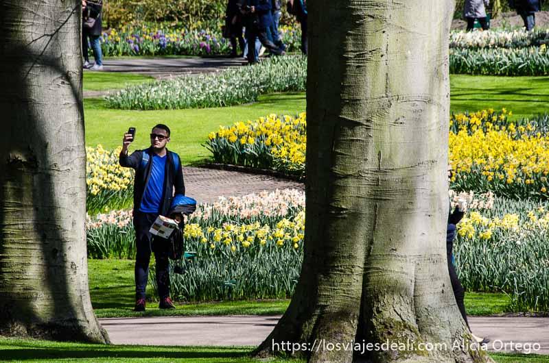 hombre haciéndose un selfie entre dos troncos de árbol grandes