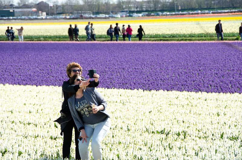 dos mujeres haciéndose un selfie enmedio de un campo de flores