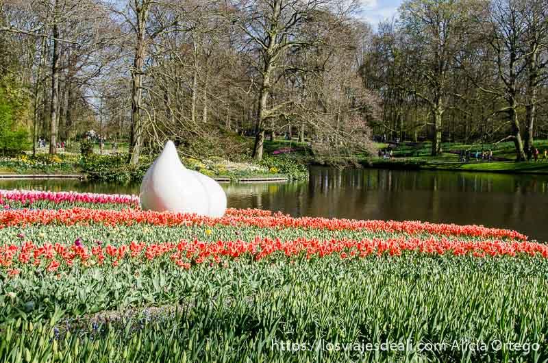 escultura que es como dos huevos blancos en medio de flores rojas junto a un estanque