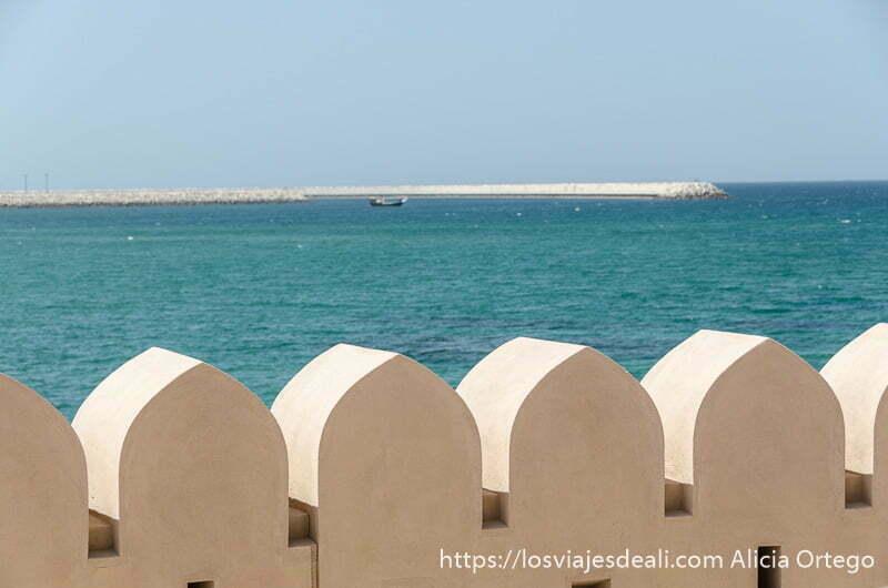 almenas en forma de arco con el mar de color turquesa detrás