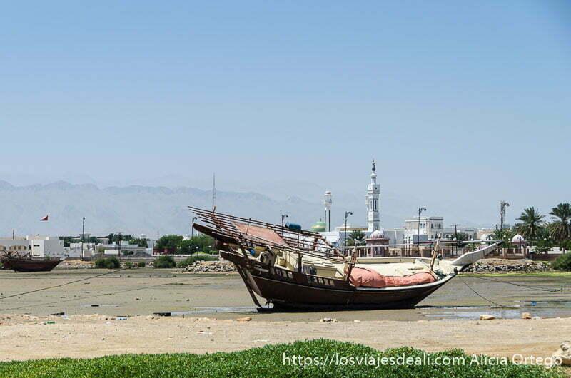 barco dhow en ensenada de arena y detrás la ciudad de simbad el marino llamada sur