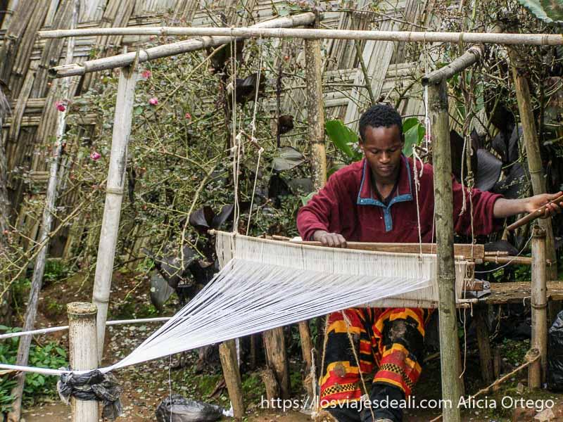 hombre de la tribu dorze tejiendo en un telar rústico