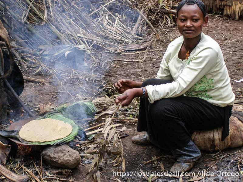 mujer dorze haciendo pan de hoja de palma sobre una hoja y fuego debajo