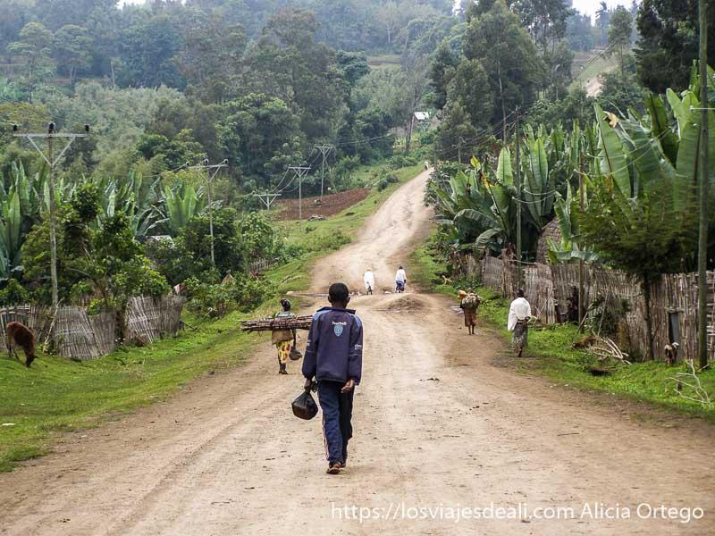 camino de barro de la aldea de la tribu dorze con vegetación a los lados y un chico andando de espaldas a la cámara en el centro