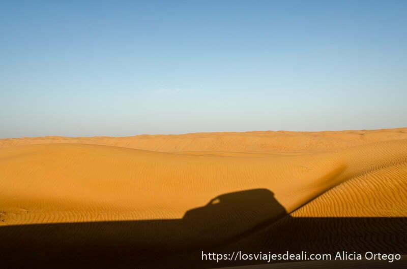 sombra de 4x4 en la arena y dunas detrás al atardecer en el desierto de wahiba