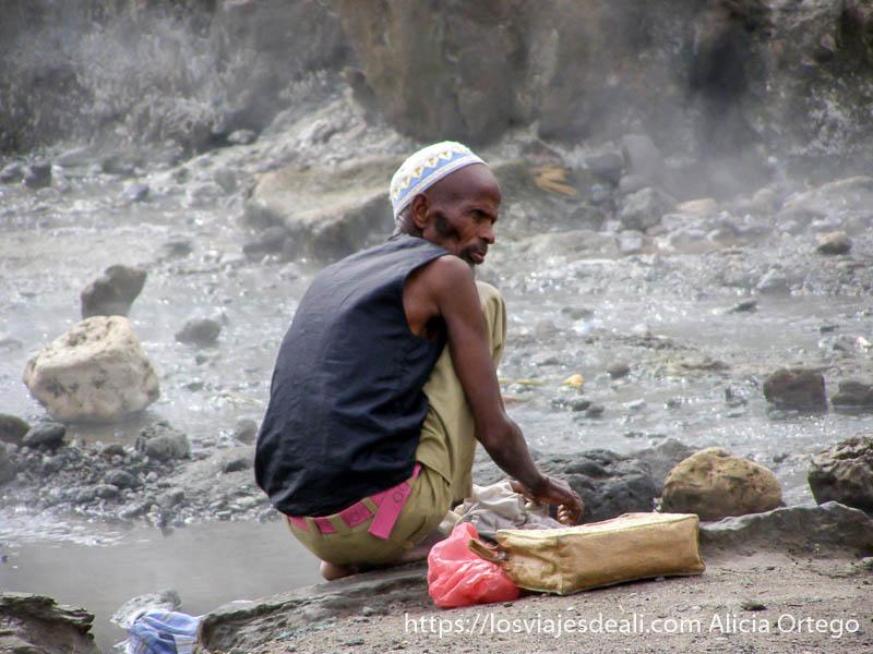 hombre lavando ropa en las aguas calientes del lago abyata en etiopía