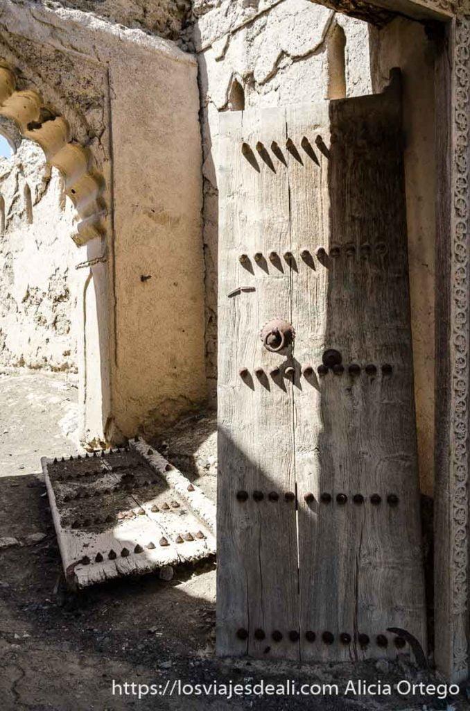 gran puerta de madera de dos hojas una de ellas caída detrás de la que se mantiene en pie en casa en ruinas de omán
