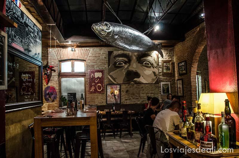 interior de restaurante con retrato de dalí en una pared y sardinas colgadas del techo