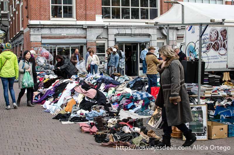 señora pasando junto a puesto de ropa usada en un montón en la calle