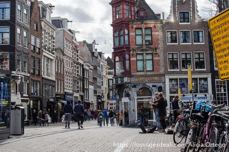 plaza de amsterdam con casas típicas muchas bicis y unos músicos