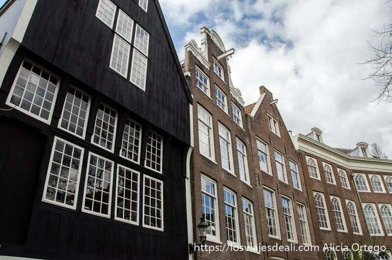 la casa más antigua de amsterdam de madera negra junto a otras de ladrillo formando una curva