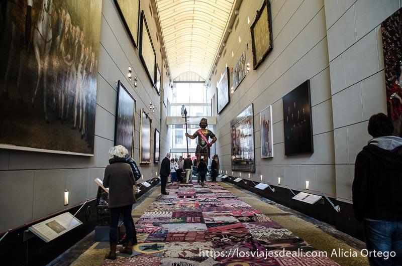 pasillo ancho del amsterdam museum con estatua gigante al fondo