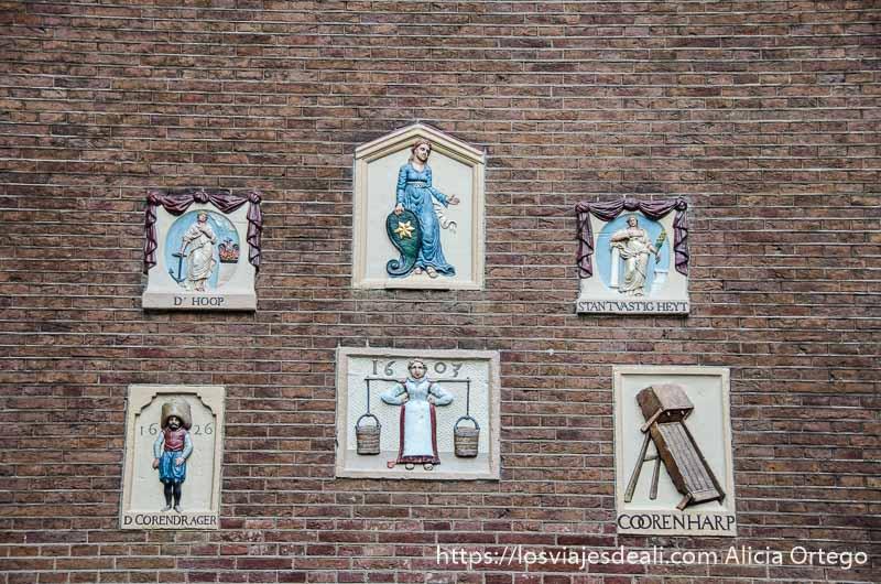 fachada de ladrillo con azulejos mostrando figuras de artesanos en amsterdam