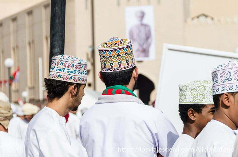 chicos omaníes vestidos con disdasha blanca y gorritos bordados y al fondo cartel del sultán