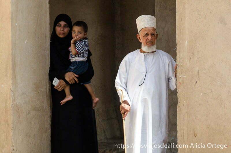 anciano omaní con bastón y mujer de negro con niño en brazos