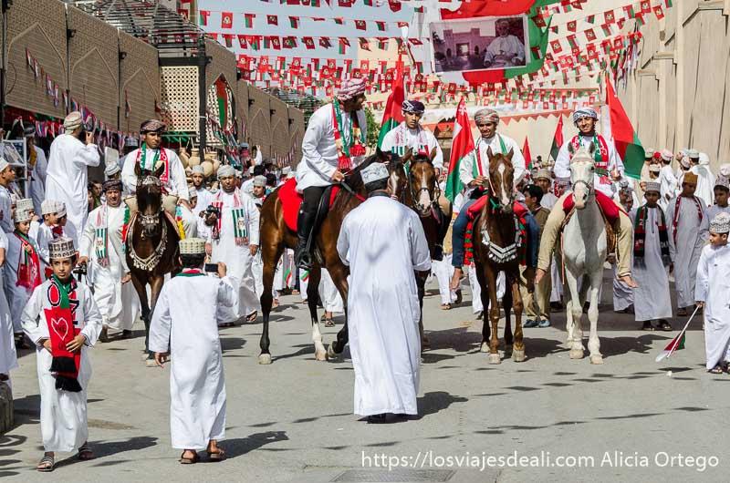 cuatro jinetes avanzando entre hombres vestidos de blanco y banderas de omán