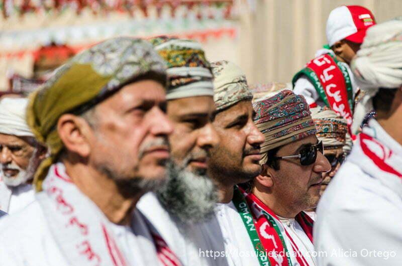 omaníes en fila con turbantes bordados