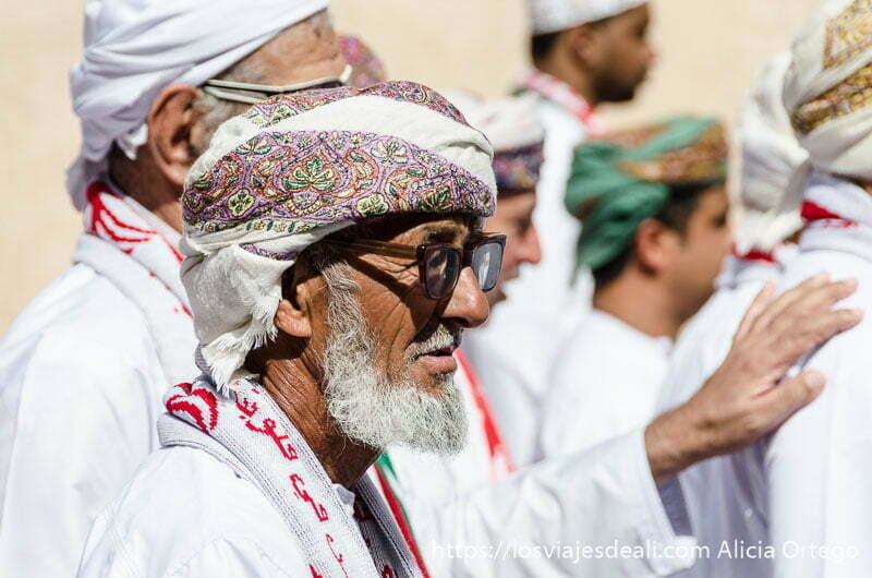 anciano omaní en el desfile con gafas de montura gruesa y barba blanca
