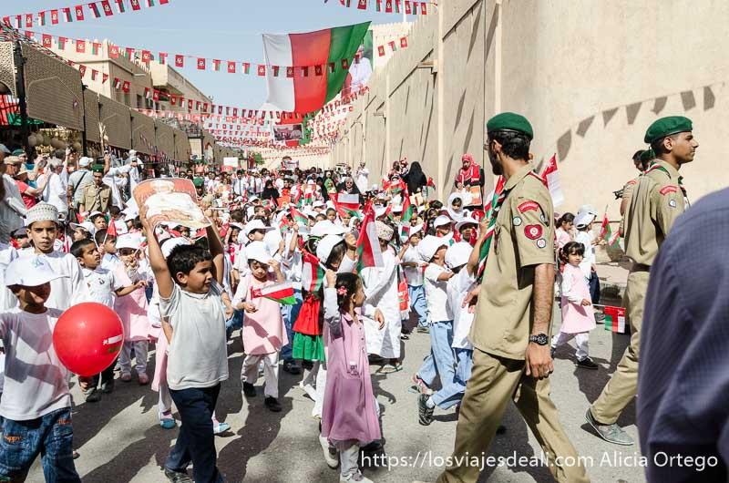 grupo de niños pequeños desfilando desordenadamente bajo hileras de banderas de omán