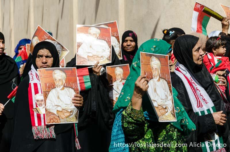 mujeres mayores con chador negro y bufandas con bandera de omán y retratos del sultán