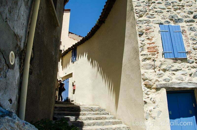 calle con escaleras que sube haciendo curva con el muro de una casa