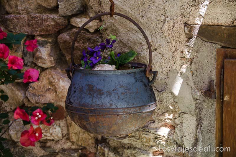 olla de hierro colgada en un muro de piedra con flores