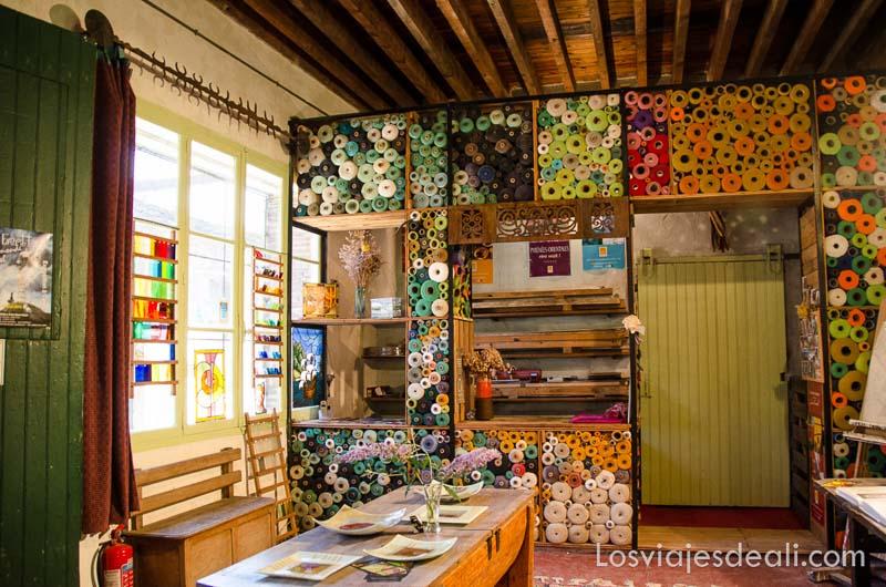 tienda con estanterías llenas de madejas de hilos de colores